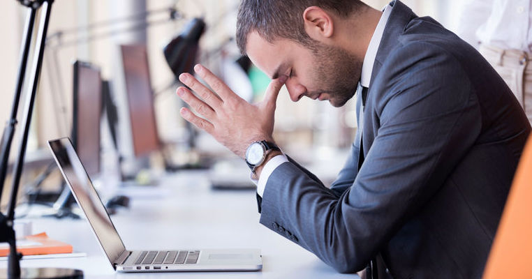 Stressed out man sitting at desk with laptop
