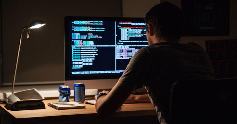 computer programmer working in a dark office