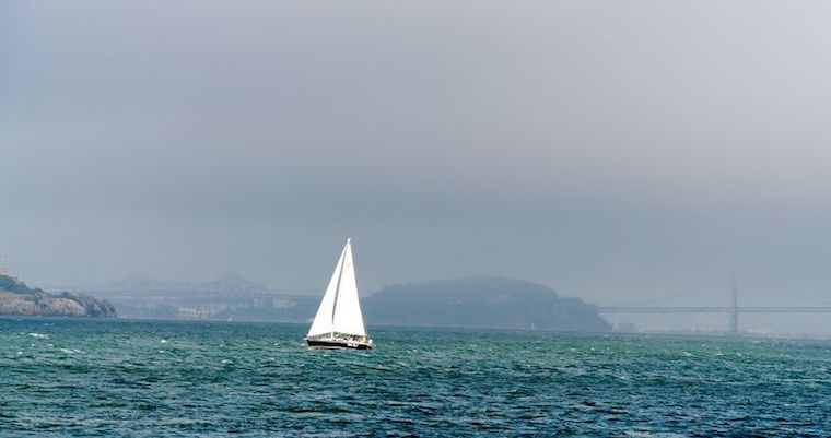 a sailboat on stormy looking water, with alcatraz and the bay bridge in the background.