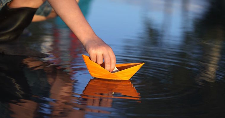 origami paper boat floating on a puddle